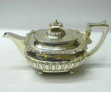 Georgian Silver Teapot  An excellent quality antique sterling silver teapot of curved rectangular form with a broad decorative border and half fluted body. The solid silver handle has a graceful classical curl to the underside. Inscribed on top with a small cursive presentation inscription and an initial. . London 1813. Maker S Hennell.