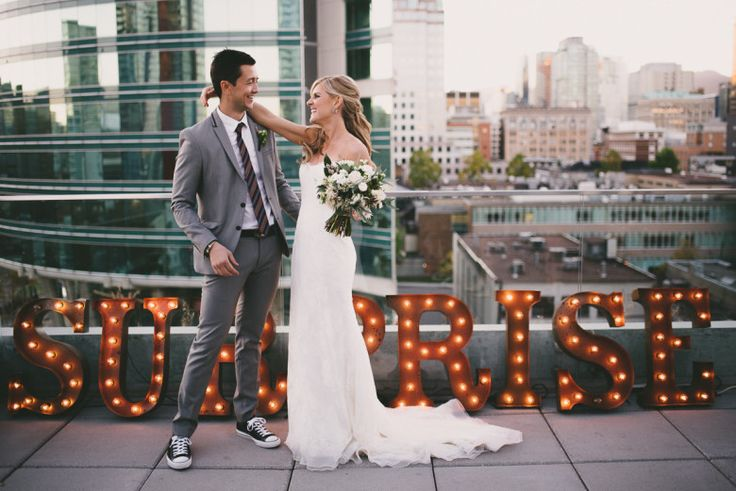 Married couple in front of surprise wedding sign on rooftop                                                                                                                                                                                 More