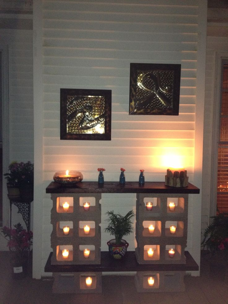 outdoor table made from cinder blocks and stained pine wood. nice ambience using the votive candles.