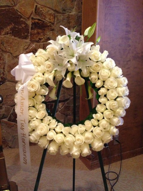 Flowers by Seasonal Celebrations. http://www.seasonalcelebrations.com  A large wreath of ivory and white roses and lilies on a floor easel.