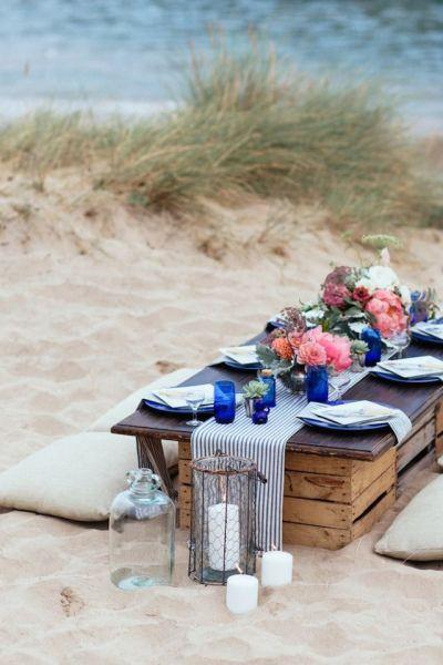 Las bodas en la playa también pueden tener un banquete tipo picnic como este
