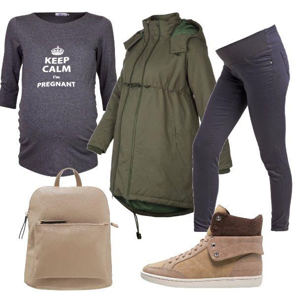 Un outfit della massima comodità, felpa con stampa grigio scuro, come i jeans con fascia per un grande comfort. Parka verde oliva, zainetto e sneakers sui toni neutri del beige e taupe.