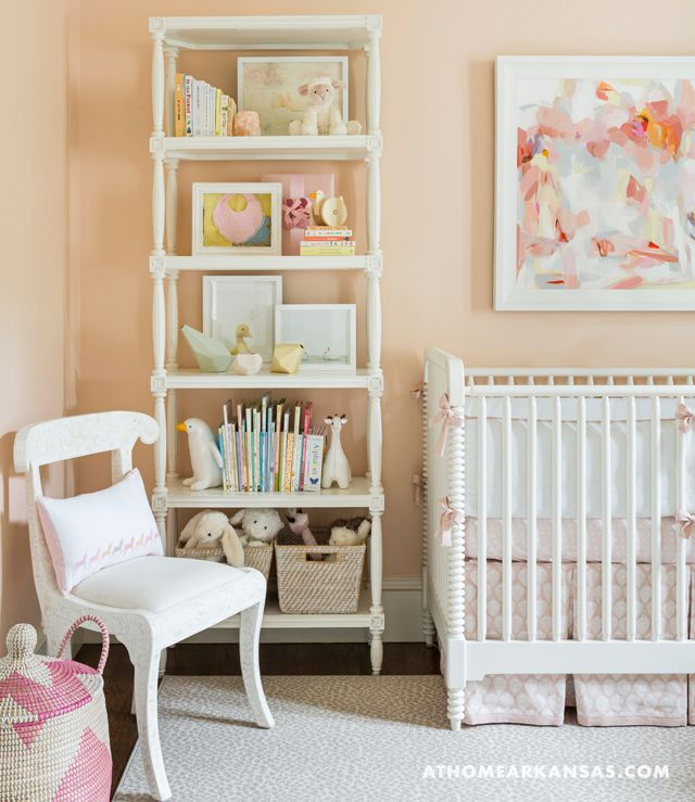 Melissa Haynes - Beautiful girl's nursery features a wall painted pinkish orange, Benjamin Moore Queen Anne Pink, lined with a pink and gray art print by Christine Baker placed over a white Jenny Lind Crib dressed in pink crib bedding placed next to a white French bookcase.
