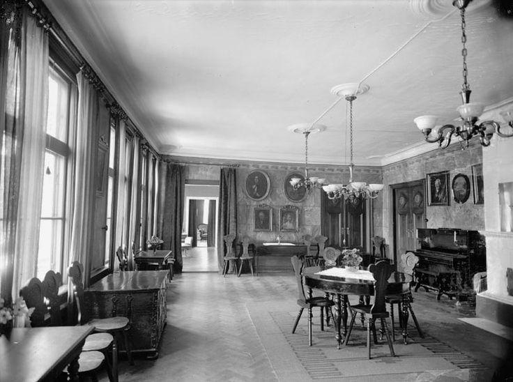 Bergkvara 1926. Interiör av en matsal.Till vänster, utmed fönstren, står några bord och stolar. I förgrunden syns en kakelugn och vid sidan om står ett piano.I mitten står ett runt bord med några stolar. I taket hänger några ljuskronor. @ DigitaltMuseum.se