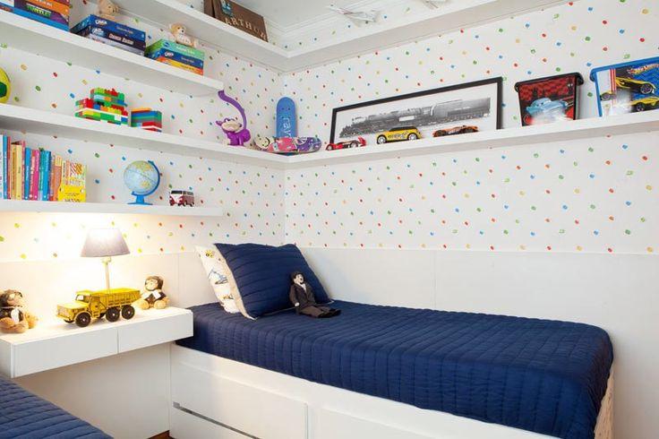 Este quarto de 8 m² possui prateleiras em todas as paredes e camas com gavetões para armazenar o que não cabe dentro do armário