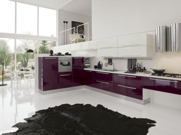 Cucina angolare moderna. Semicolonne e basi in finitura viola lucido, pensili bianco lucido con piano di lavoro in laminato squadrato bianco.