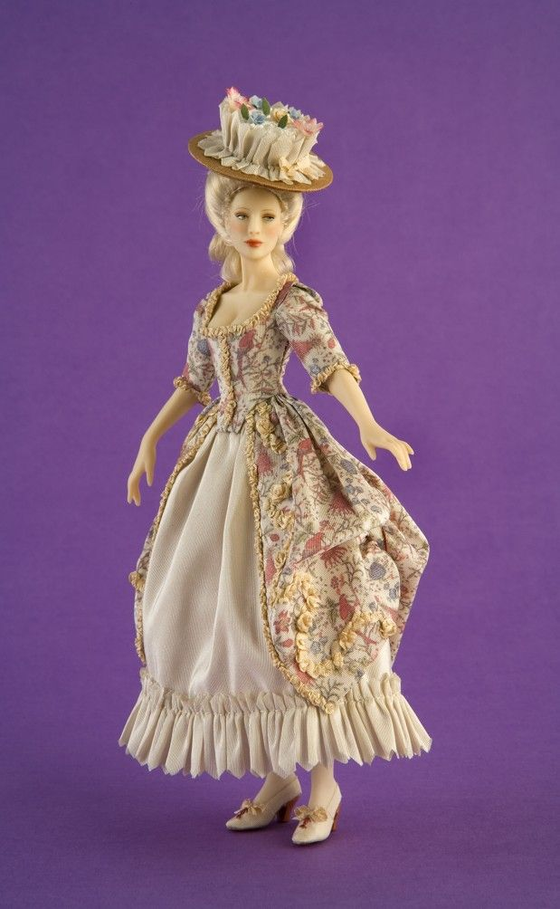 NAME: Valentine - PERIOD: 1775-1785. Dress inspired by a robe á la polonaise in the Snowshill Manor Collection (England). It is made out of taffeta silk, exclusively printed for Carabosse Dolls by Les Chinoiseries with a design of the era. The doll wears silk slippers trimmed with embroideries.