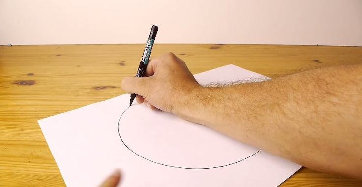 This is how you draw the perfect circle. Pen and paper on a wooden table- Froot.nl