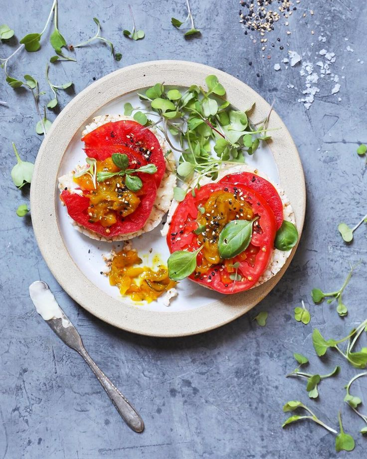 Some sunshine on a cloudy day (sorry couldn't help myself)! Beautiful sweet and loaded with sun ripened flavor summer heirloom tomatoes are my go to (this one is so pink ). I simply love them on rice cakes with a smear of vegan mayo a few flakes of sea salt fresh ground pepper and a sprinkle of gomasio. If you happen to have any delicious savory preserves (like mouthwatering zucchini relish visit cloudykitchen.com for the recipe @cloudykitchen). Micro greens and fresh herbs scattered about…