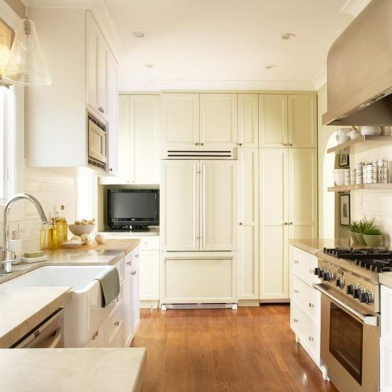 small kitchen  +floor to ceiling cabinets around refrigerator  +TV  +open shelves by range