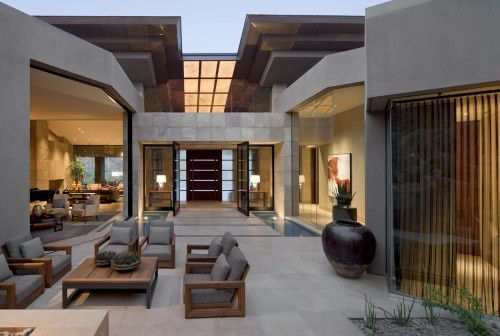 The front door is aligned with an expanse of glass that opens out to the backyard and a view of the hillside. The grid of onyx hovering overhead emphasizes the axis from the front entry to back. The water also emphasizes the connection from the hillside waterfall to the fountai