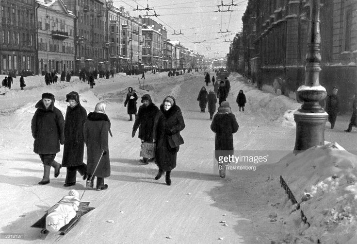A woman carries away a corpse on a sledge down Nevski Prospect, Leningrad's main avenue, during the siege of Leningrad when many died of starvation.
