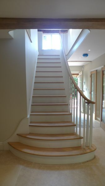 Elspeth Beard,creative architect and a home counties listed property designer,came up with this continuous free form handrail design / staircase for a client with very specific requirements. The result was a classical ground floor staircase leading up to a single room attic conversion helix staircase, both of which had cut string, hand carved oak handrails.