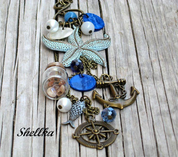 Náhrdelník+,,LETNÍ+VZPOMÍNKY,,+IV.+Náhrdelník+vyrobený+ve+stylu+vintage.+Větší+esíčko,+na+němž+je+zavěšena+velká+mořská+hvězdice,ručně+patinovaná+sv.modrou+a+bronzovou+patinou+na+kov.Na+dalších+třech+řetízcích+se+pohupují+větší+kotva,kompas,rybička-patinována+sv.modrou+patinou+na+kov,doplněno+penízky+bílé+a+modré+barvy,bílá+perlička,modré+korálky...