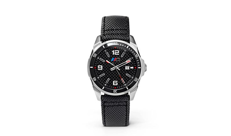 BMW M Uhr: Mehr Sport. Auch am Handgelenk. Die Armbanduhr mit hochwertigem Edelstahlgehäuse sowie einer schwarzen Aluminium-Lünette und Carbon Zifferblatt besitzt als Highlight ein Schweizer Quarz-Uhrwerk von RONDA mit analoger Datumsanzeige. Für Langlebigkeit sorgen das gehärtete Mineralglas und ein robustes Armband mit Lederinnenseite.