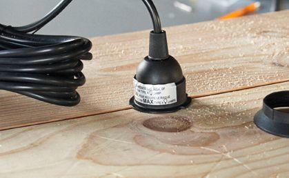 Paso 7:  Una vez que se seque la pintura o laca, pase el accesorio de iluminación a través de el agujero superior. Inserte su bombilla dentro de la caja.