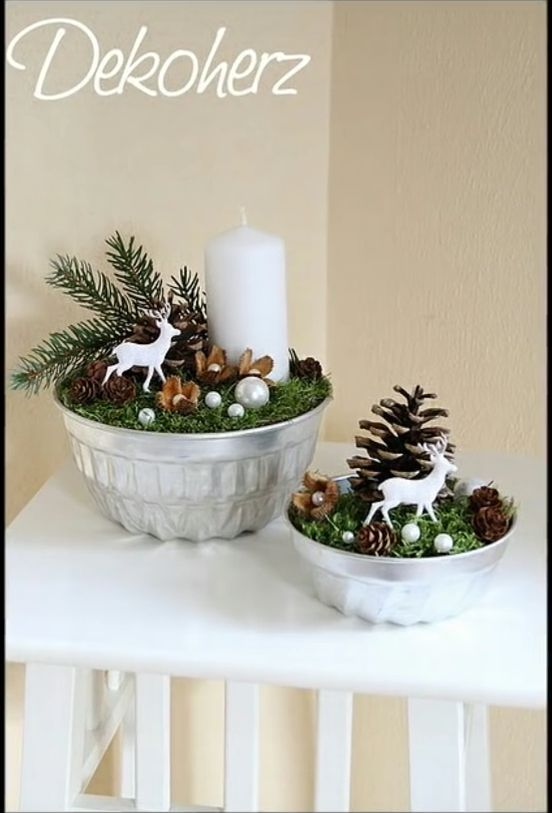 silver bowls with moss, small ornaments, deer, pinecones, candles, sprigs of evergreen