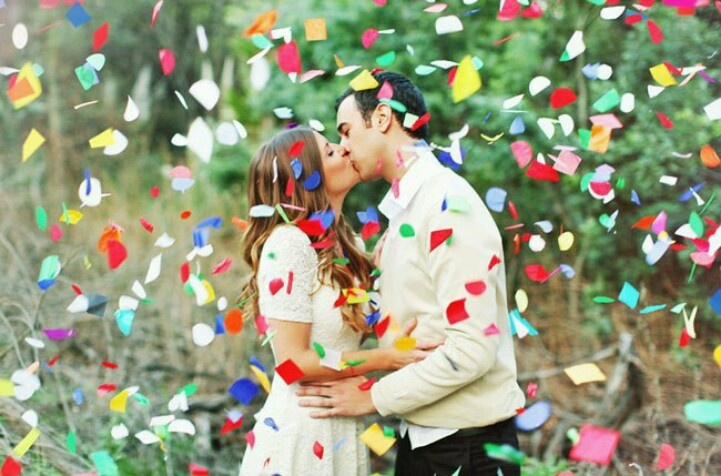 happy couple in confetti engagement photoshoot