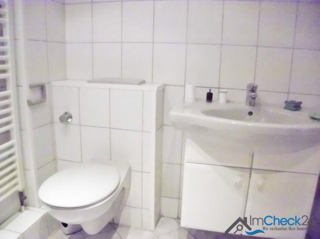 Das Bad verfügt über eine gut gepflegte Sanitärausstattung im schlichten Weiß.
