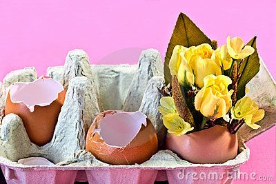 an egg carton with brown eggs shells one of which is filled with yellow silk flowers.