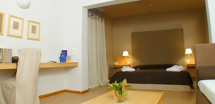Junior Suite with an open-plan bedroom and sitting area, situated in the gardens of Minos Beach Art Hotel
