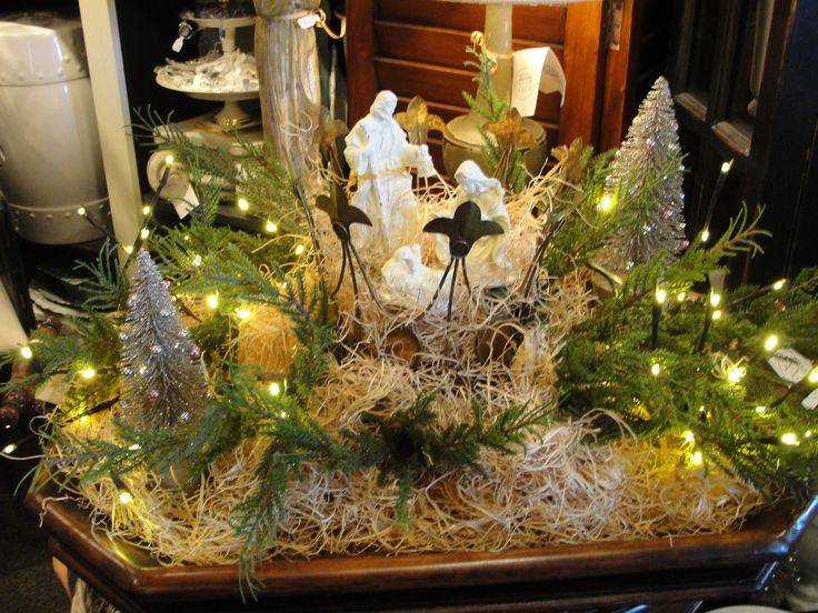 nativity tray with mini trees and cedar. nativity figurines placed inside of crown.