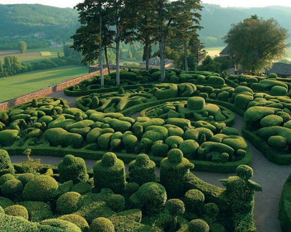 """The Overhanging Gardens of Marqueyssac, Vézac, France: """"This French garden, which sits on a cliff overlooking a river, is actually a complex system of labyrinths carved from over 150,000 boxwood trees. From above, the round shapes make it look bulbous and cartoonish, like somewhere Alice would find herself after a long visit with the caterpillar."""""""