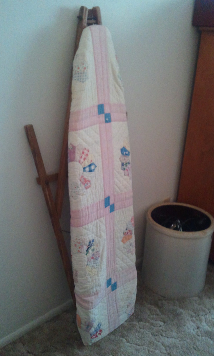 A tattered quilt made a nice, decorative ironing board cover.  The old crock stores the iron.