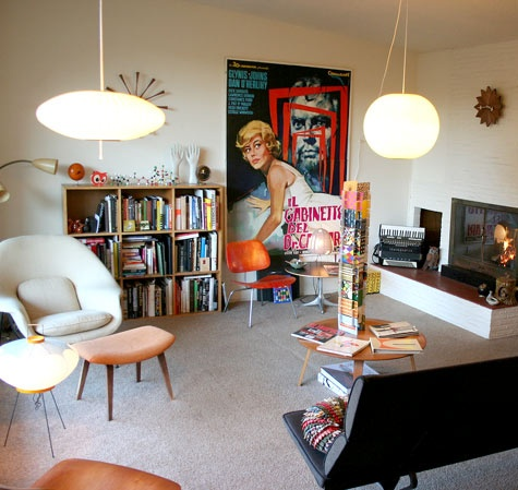 This room has large light fixtures, bold colors on the chairs and books, and looks outdated