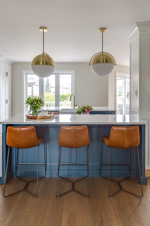 charming Cb2 Kitchen Island Part - 18: Brass and white glass globe pendants, CB2 Globe Pendant Lights, hang over a  blue kitchen island topped with a white quartz countertop seating three  orange ...