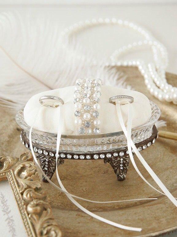 結婚式や挙式後、指輪をのせておくリングピローです。アンティーク調のガラストレーにビジューをあしらったリングクッションをのせました。パールとクリスタルの繊細なデザインに心くすぐられるデザインです。指輪は左右についているリボンに結び使用するので落ちる心配はありません。**オリジナルギフトBOXに入れてお届け致します**おしゃれなギフトBOXなので、結婚お祝いのプレゼントにもピッタリです。(BOX画像の中身はサンプルです)size ::: 約 W.11.5cm x D.7.5cm x H.6cm材質 ::: アイアン、ガラス ※商品画像はブラウザにより色の見え方が違うため 実際の色とは異なる場合がございますのでご了承ください。