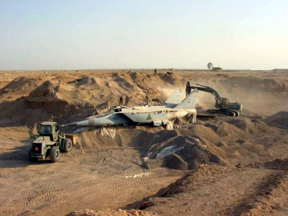 030706-F-0000C-907 A U.S. military search team uncovers a MiG-25R Foxbat-B from beneath the sands in Iraq on July 6, 2003.  Several MiG-25s and Su-25 aircraft have been found buried at Al-Taqqadum airfield west of Baghdad.  DoD photo Master Sgt. T. Collins, U.S. Air Force.  (Released)