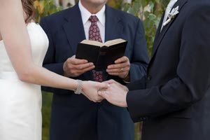 Bride and Groom holding hands at the altar as the minister oversees the reading of the vows. - Kristine Foley/Digital Vision/Getty Images