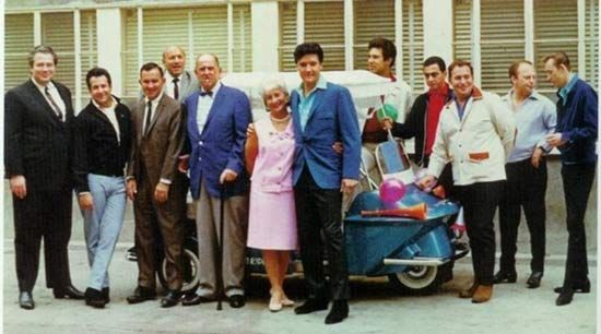 Left to right: Ray Sitton, Joe Esposito, (unknown), Bullets Durgam, Colonel Parker, Mrs. Parker, Elvis, Larry Geller, George Klein, Alan Fortas, Marty Lacker, Richard Davis – in front of the Colonel's office at MGM Studios