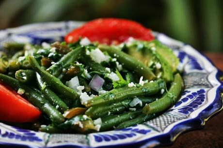 Mexican green bean salad with fresh green beans, cilantro, jalapeno, red onion, cotija cheese, avocado, tomato, olive oil and lime juice.