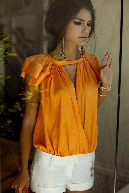 beautifully draped orange blouse paired with crisp white shorts