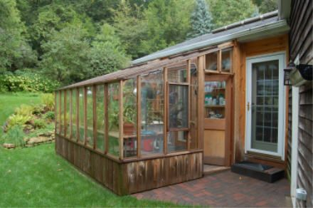 greenhouse off the side of the house - stones that match the front of the house at the bottom, old windows on the top & roof