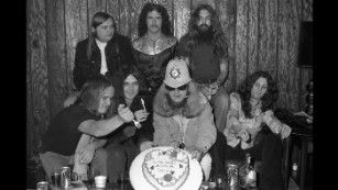While backstage, the band enjoys a cake from MCA Records. From left are Van Zant, Ed King, Rossington, Billy Powell, Leon Wilkeson, Pyle and Collins.