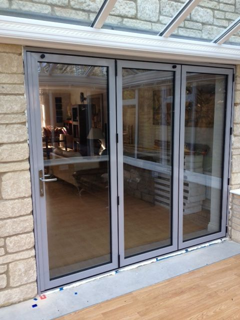 a set of three door bi-folds in light grey in a conservatory