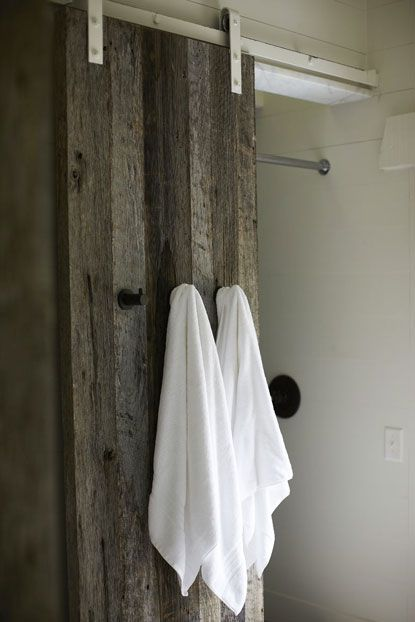 I love two things here--the use of a sliding barn door on a shower (clearly reclaimed wood here) and hooks on the sliding door--points for practicality.