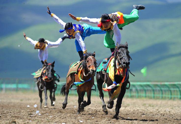 Tiga pria beraksi dalam festival menunggang kuda tradisional di Ngawa, Sichuan, China.