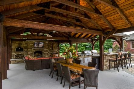 This outdoor entertaining space features an open pavilion with TV, kitchen and fireplace. The nearby pool provides a great place for cooling off.