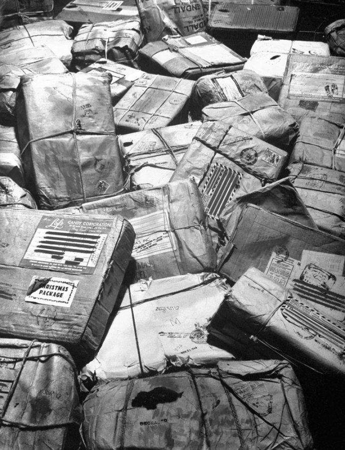 """In New York City, piles of Christmas packages meant for American servicemen who have been listed as missing or killed in action await for """"Return to Sender"""" stamps, 1944. You can see the words """"missing"""" or """"deceased"""" stamped on some of the packages on the bottom of the photograph."""
