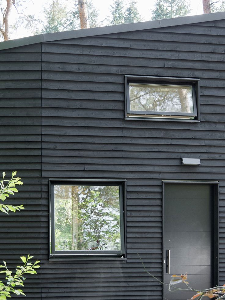 Thin external wood architraves around black aluminium windows, on a weatherboard house.