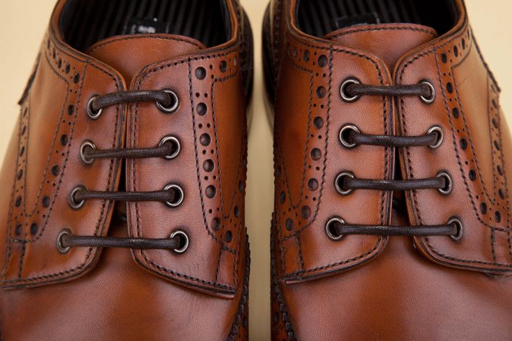 The refined Full Brogue wingtip with additional decorative perforations in the center of the toe cap valorizes the sophisticated lines of an evergreen classic. - La raffinata decorazione punzonata Full Brogue, con motivo a coda di rondine e fiore in punta, valorizza le linee sofisticate di un classico sempre attuale.
