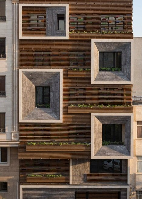 Faceted window frames project from the slatted timber and stained-glass facade of this apartment block in Tehran