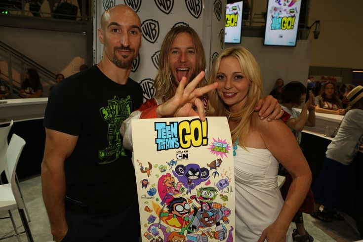 TEEN TITANS GO! stars Scott Menville (left), Greg Cipes and Tara Strong -- who voice the characters of Robin, Beast Boy and Raven, respectively -- hold up one of the posters they're signing at the Warner Bros. booth at Comic-Con 2014. #WBSDCC