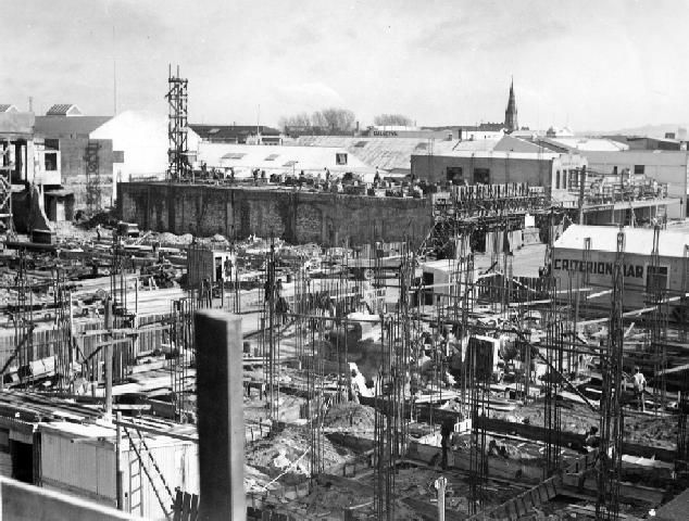 The photograph shows that the devastation caused to the Napier central business district by the 3 February Hawke's Bay earthquake has been cleaned up and new building begun.  In the foreground of the photograph shows the construction of the Criterion Hotel on the corner of Hastings and Emerson Streets. The temporary Criterion bar can be seen behind the new building. The spire of St Patrick's Catholic Church can be seen in the distance on the right.  Photographer, A B Hurst, Napier.