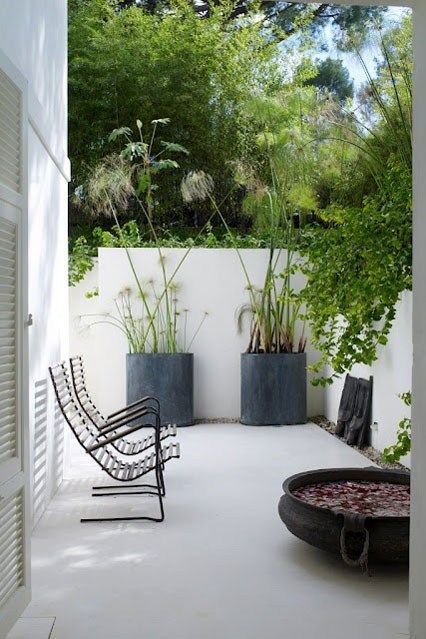Minimalist garden inspiration with white painted concrete walls and pavement, large scale grey pots of sculptural plants (alliums work well here) and slatted wooden furniture to give a feeling of space. A simple and beautiful garden space.