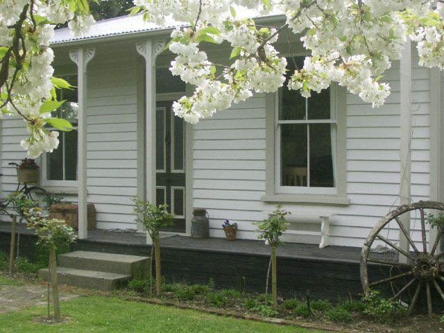 An addition to an historic cottage. Resene colourings, like Sakura blossom tree, dark balcony.